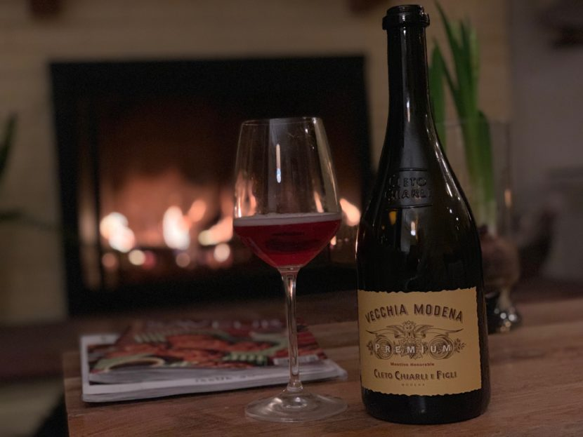 A bottle of Lambrusco and a glass of Lambrusco in front of a fire in a fireplace in Boulder, Colorado